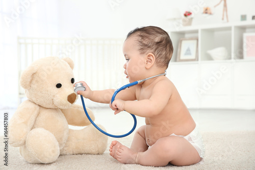 Canvastavla  Cute little baby with stethoscope and toy bear playing at home