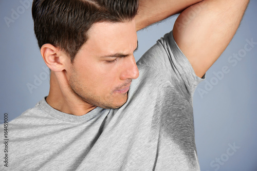 Photo Handsome young man with wet spot on clothes under armpit against grey background