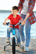 Young woman teaching her son to ride bicycle outdoors near river