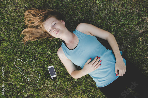 Poster Ontspanning Relaxing outdoor. Young woman relaxing in the park after running
