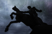 Silhouette Of Statue The Tamers Of Horses  On The Dark Sky Background, View Through Wet Window