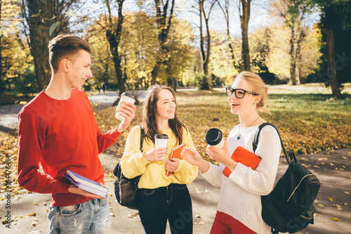 Photo  Three students with disposable cup laughing together in a park - season, study, education and people concept