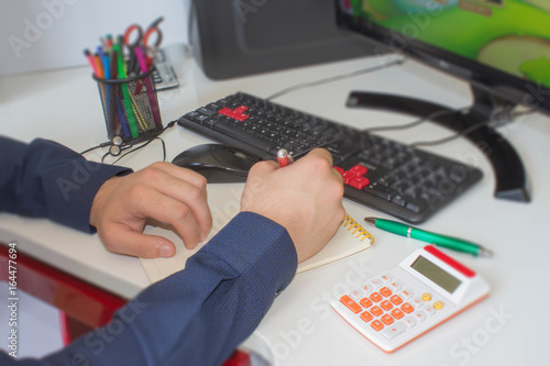 Fototapeta Close up young man with calculator counting making notes at home, hand is writing in a notebook obraz na płótnie
