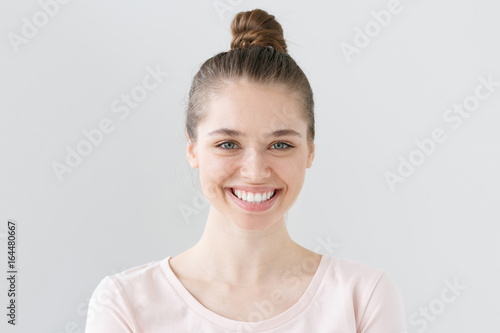 Cuadros en Lienzo Indoor portrait of young attractive green-eyed female without makeup isolated on grey background in daylight smiling widely and happily, looking open and satisfied with communication and life