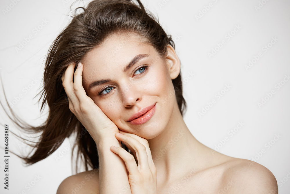 Fototapeta Beautiful naked young girl with perfect clean skin smiling touching hair over white wall. Facial treatment.