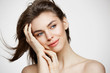 Beautiful naked young girl with perfect clean skin smiling touching hair over white wall. Facial treatment.