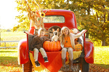 Kids And Puppy On Back Of Truck In The Fall