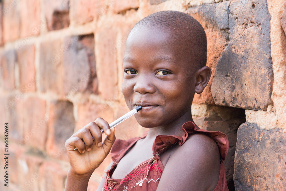 Fototapety, obrazy: An 11-year old black Ugandan girl smiling and holding a pen against her mouth and leaning against a brick wall looking at the camera