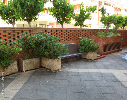 Papiers peints Jardin Bench and bushes with brick fence in the city park or backyard home