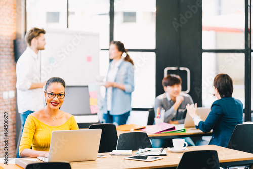Fotografia  Smiling Asian woman using laptop computer, with young multiethnic business colleagues working together in background