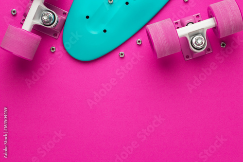 Photo  plastic mini cruiser board disassembled on deep pink with background copy space