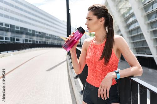 Spoed Foto op Canvas Fitness Pensive female runner drinking water outdoor
