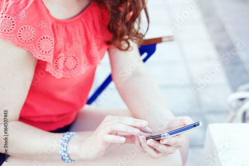 Fotografía  Unrecognizable young woman sitting outdoors and using a smartphone; selective fo