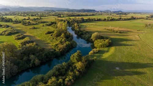 Foto auf Gartenposter Fluss Aerial view of river bending across fields at sunset.