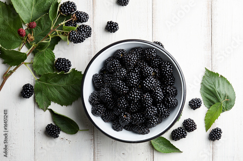 Bowl of fresh ripe blackberries on textured stone background