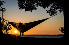 A Person Enjoying The Sunset In A Hammock