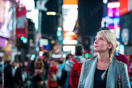 Fotografering  Impressed Woman in the Middle of Times Square at Night,