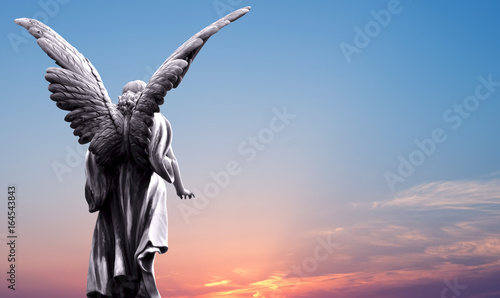 Foto  Angel sculpture over bright sky
