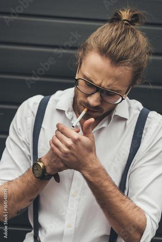 Fotografie, Obraz  Close-up handsome stylish man in eyeglasses lighting cigarette with lighter