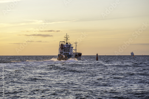Motorboot verlässt den Hafen im Sonnenuntergang Poster