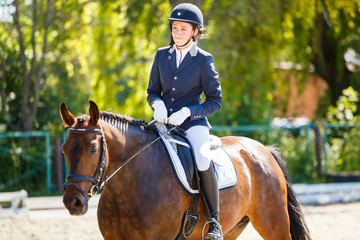 Young rider girl on bay horse at dressage equestrian competition