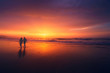 canvas print picture - couple walking on beach at sunset