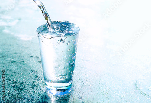 A stream of clear transparent cold water is poured into a glass beaker on blue background with beautiful lighting close-up. Water glows in a glass.