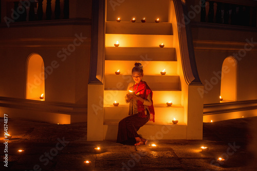 Foto op Plexiglas Wand Asian woman wearing traditional thai culture with light candle in temple on after sunset,vintage style,Thailand
