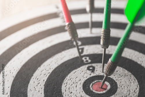 Fotografía  dart arrow hitting in the target center of dartboard,abstract of success