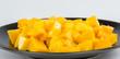 Mango chunks on black plate isolated on white background