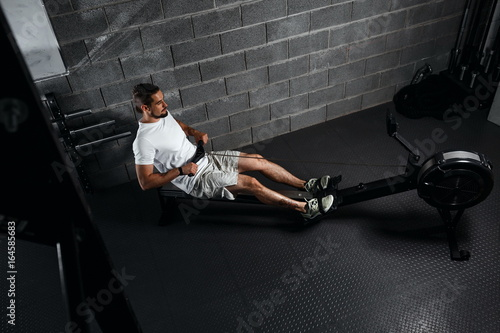 Fotografie, Obraz  Fitness young man using rowing machine in the gym