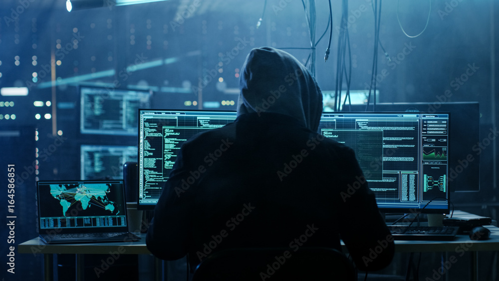Fototapeta Dangerous Hooded Hacker Breaks into Government Data Servers and Infects Their System with a  Virus. His Hideout Place has Dark Atmosphere, Multiple Displays, Cables Everywhere.