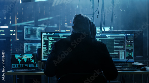 Photo Dangerous Hooded Hacker Breaks into Government Data Servers and Infects Their System with a  Virus