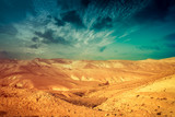 Mountainous desert with colorful cloudy sky. Judean desert in Israel at sunset