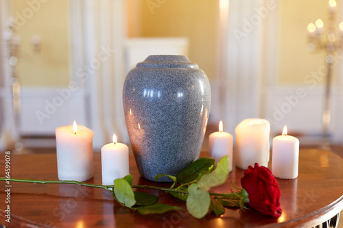 Foto red rose and cremation urn with burning candles