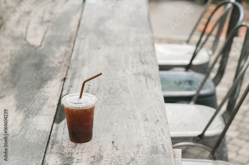 Staande foto Thee Cold black coffee drink with ice in plastic cup on wooden table with chairs in garden background