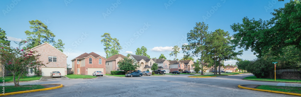 Fototapety, obrazy: Suburban residential area, row of modern townhomes in Humble, Texas, US. Red brick houses surrounded with tall pine trees, cloud blue sky. Panorama view street intersection and multi-story townhouses.