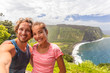 Selfie couple tourists at Waipio Valley lookout in Big Island, Hawaii. Happy smiling people taking self-portrait picture with camera phone. Woman and man taking photos on adventure nature travel.
