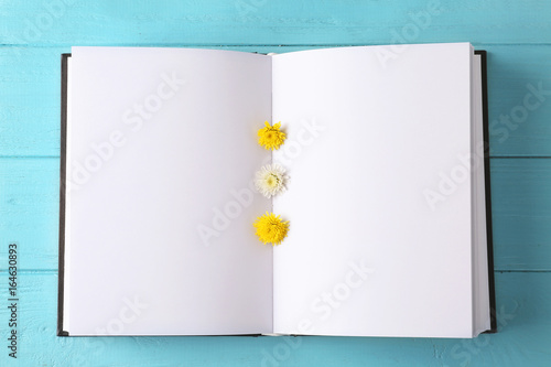 Fotografía  Open book with blank pages and beautiful flowers on color wooden background, clo