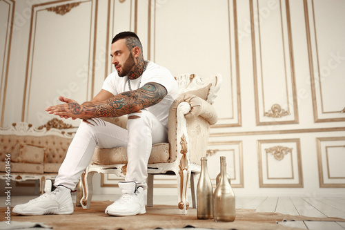 Fotografía  Sexy closeup portrait of Elegant handsome male model with fashion tattoo and a black beard sitting in chair in white casual clothes in hotel interior with gold decor
