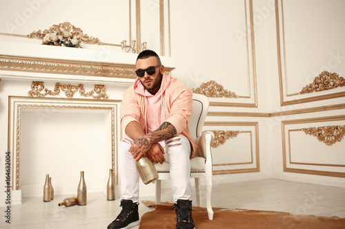 Sexy closeup portrait of Elegant handsome male model with fashion tattoo and a black beard sitting in chair in white casual clothes in hotel interior with gold decor Tapéta, Fotótapéta
