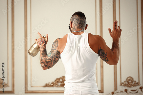 Fotografía  Sexy closeup portrait of Elegant handsome male model with fashion tattoo and a black beard standing back in white casual clothes in hotel interior with gold decor