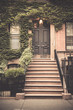 Ivy covered exterior door on New York City brownstone apartment Building with vintage tone