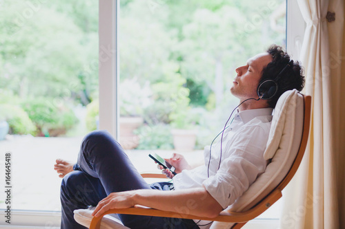 Fényképezés listening relaxing music at home, relaxed man in headphones sitting in deck chai
