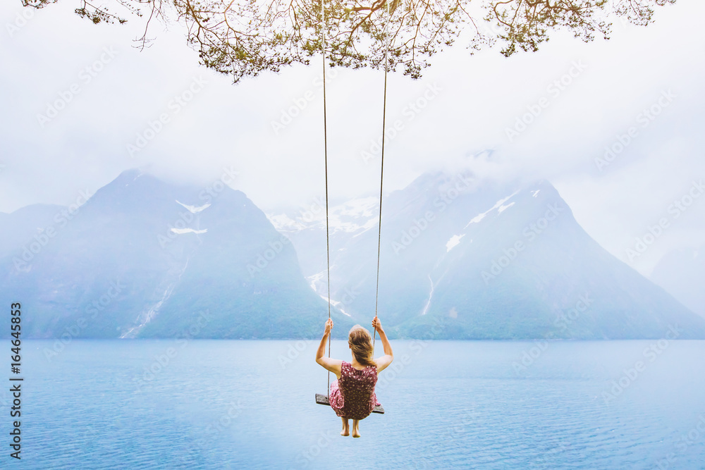 Fototapeta dream concept, beautiful young woman on the swing in fjord Norway, inspiring landscape