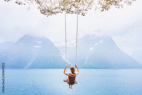 Fototapeta dream concept, beautiful young woman on the swing in fjord Norway, inspiring landscape obraz