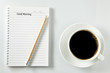 White cup of coffee morning on wooden table with notebook