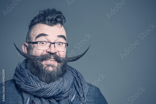Obraz Smiling bearded man with a mohawk hairstyle and a very long mustache on a gray background - fototapety do salonu