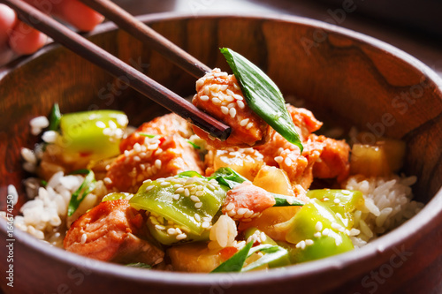 Photo  Asian cuisine - rice in sauce with stir fried vegetables, pineapple and salmon