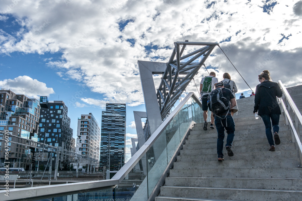 People walking over bridge to the business area at Bjørvika in Oslo, Norway with a modern Scandinavian architecture with glass windows